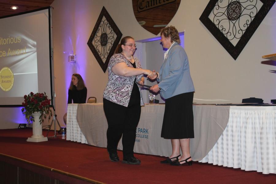 Moraine Park student shaking hands with Bonnie Baerwald
