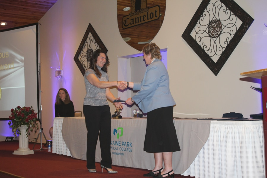 Carla Stephany shaking hands with president Bonnie Baerwald at student awards banquet