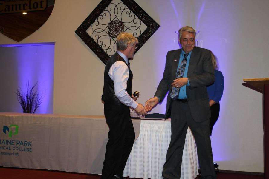 Dewayne Sexton shaking hands with Dr. Stan Cram