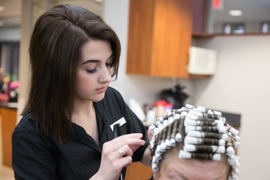 Female cosmetology student works on customer hairstyle in Moraine Park salon