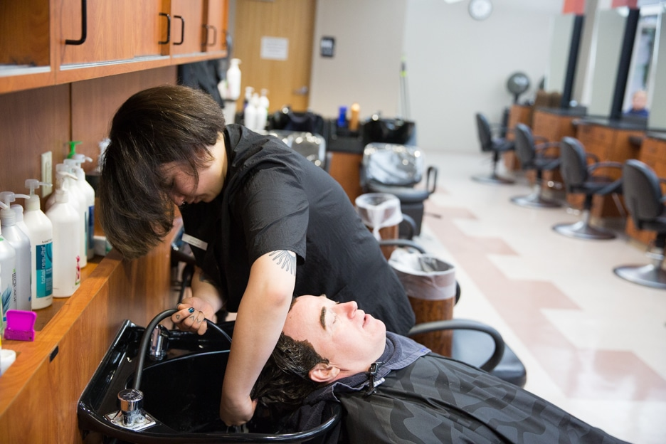 Moraine Park cosmetology student washes man's hair in salon