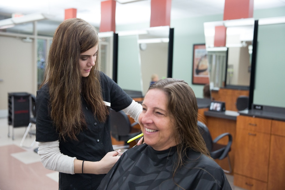 Female cosmetology student works on customer haircut at Moraine Park salon