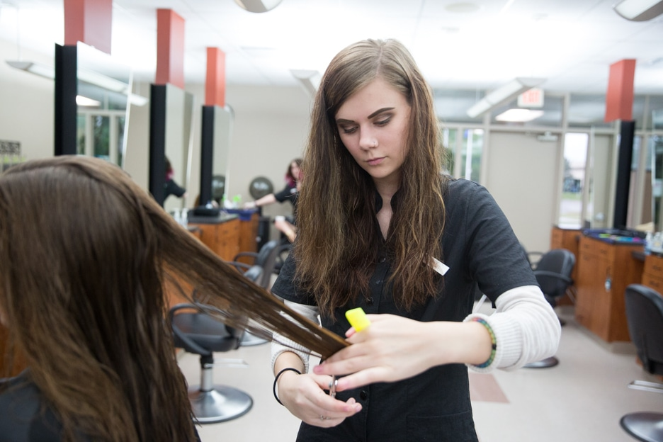 Cosmetology student combs through customer hair at Moraine Park salon