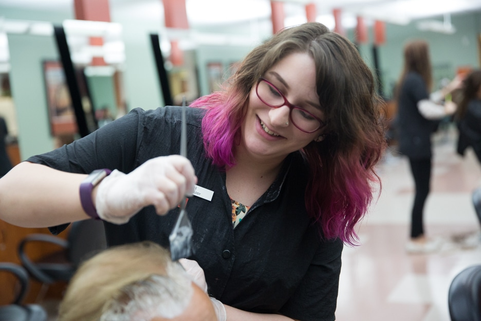Moraine Park cosmetology student works on hairstyle of male customer in salon