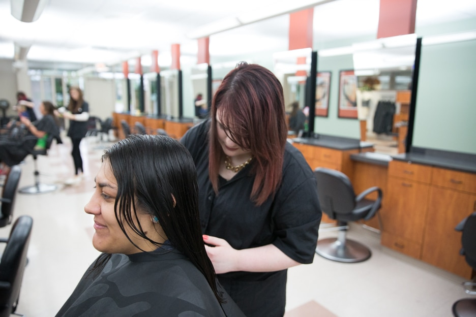 Female cosmetology student works on hairstyle of customer at Moraine Park