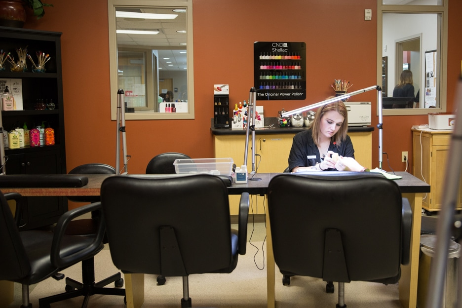 Female cosmetology student practices at a manicure station in Moraine Park salon