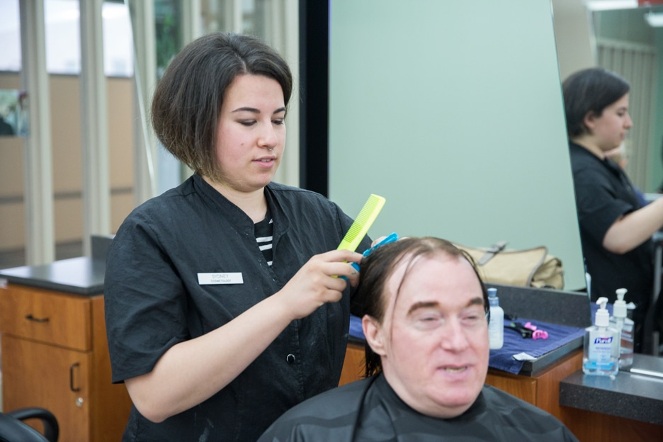 Female student works on man's hair in Moraine Park cosmetology class