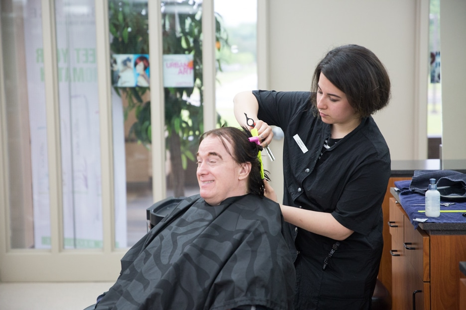 Female student works on male haircut in Moraine Park cosmetology class