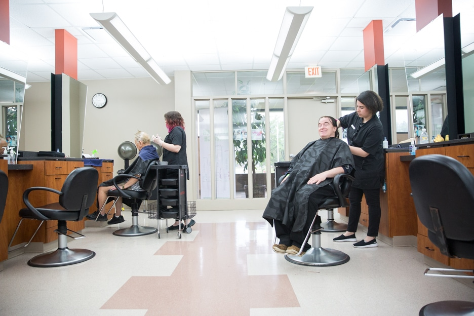 Cosmetology students work on row of customers in Moraine Park Fond du Lac salon