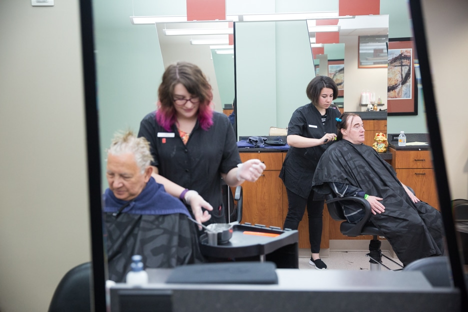 Two female cosmetology students work on customer haircuts in Moraine Park salon
