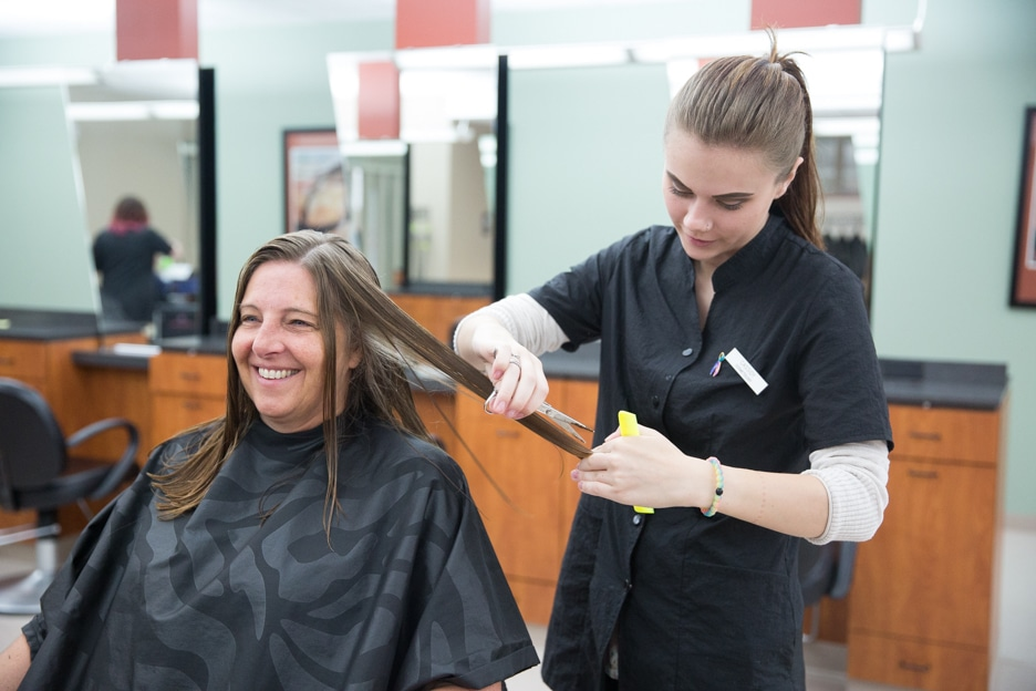 Customer smiles as female Moraine Park cosmetology student cuts hair in salon