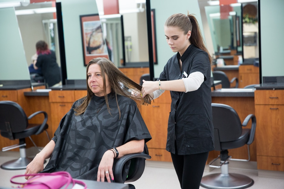 Female cosmetology student works on haircut of female customer in Moraine Park salon