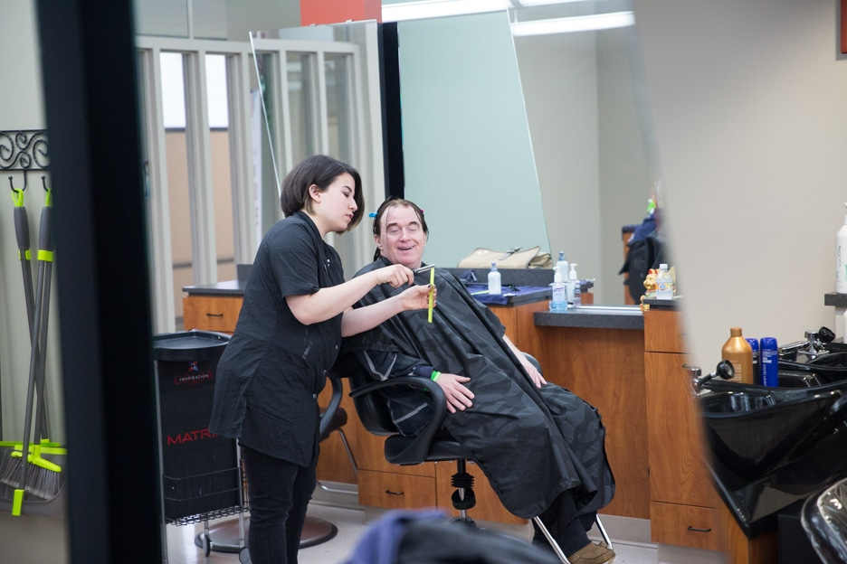 Female cosmetology student works on gentlemen's haircut in Moraine Park salon