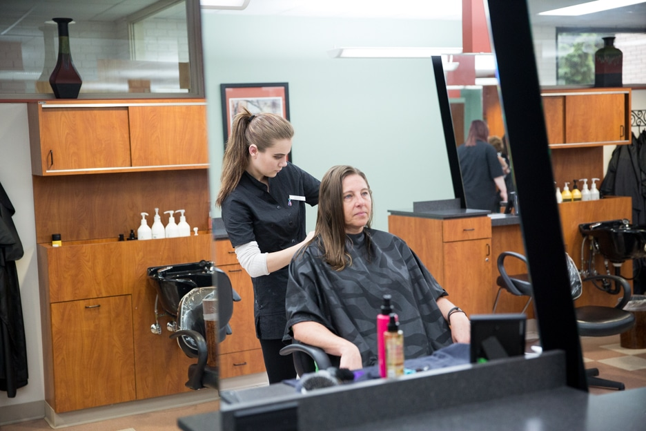 Moraine Park cosmetology student works on hair style of customer