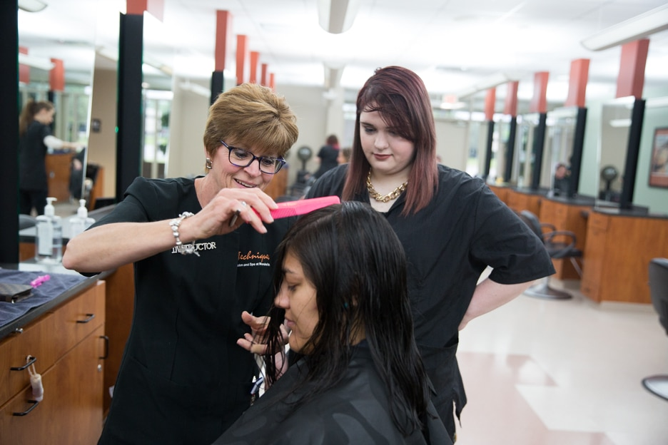 Instructor Eileen Bouchard inspects student haircut in cosmetology class