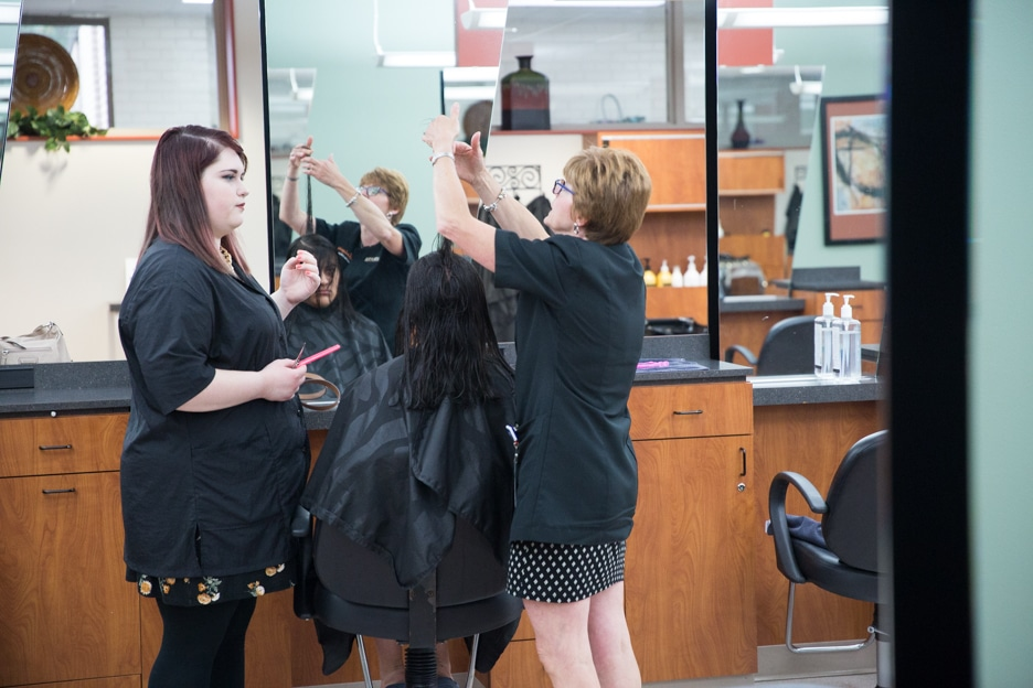 Female instructor inspects cut during cosmetology class at Moraine Park in Fond du Lac