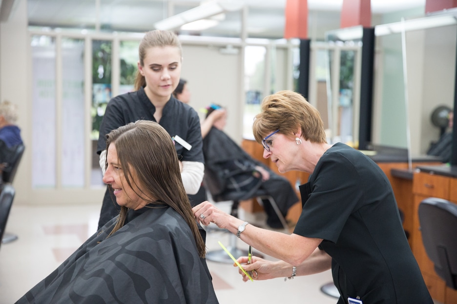Instructor Eileen Bouchard inspects haircut in Moraine Park salon