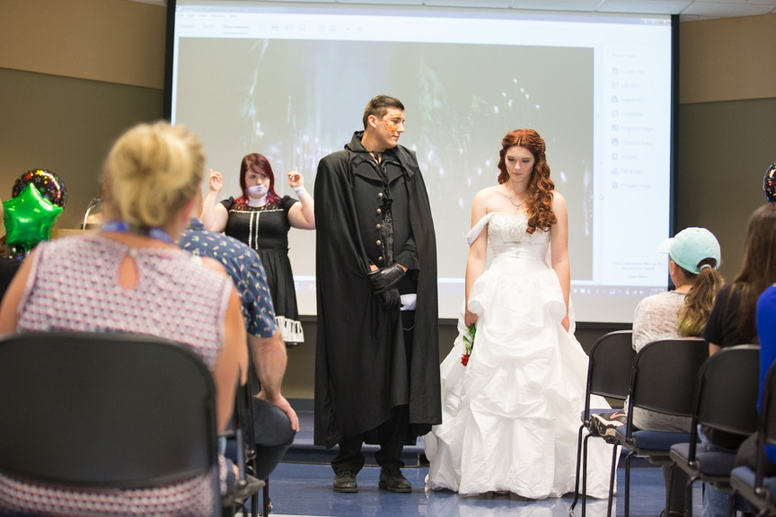 Student discusses styles of male and female model dressed as Phantom of the Opera characters