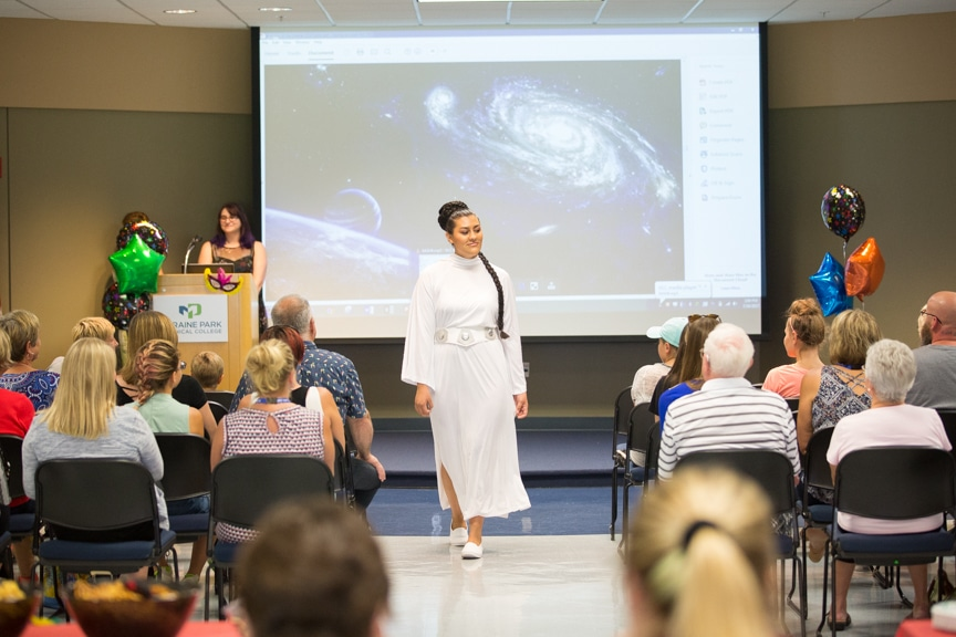 Model walks down runway at Moraine Park fashion show wearing Star Wars-inspired white robe