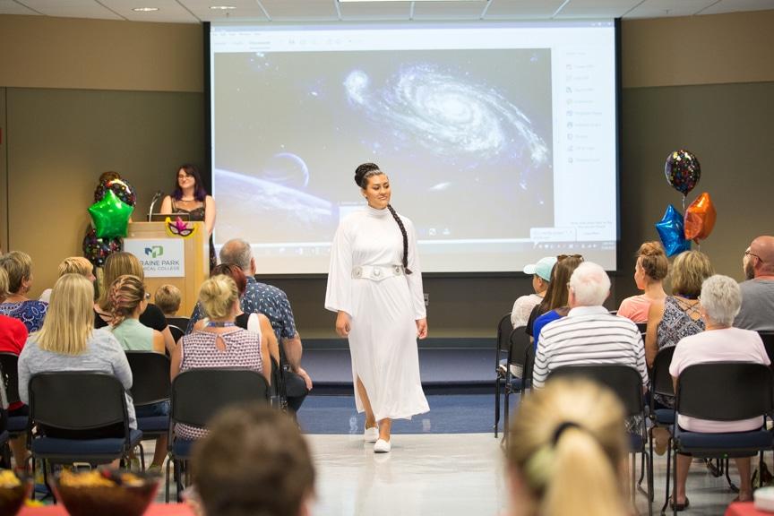 Model walks down runway at Moraine Park fashion show wearing Star Wars-inspired white robe