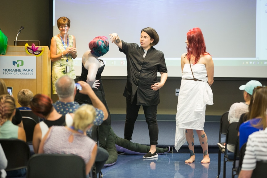 Student explains hairstyles while Little Mermaid-inspired models stand nearby at Moraine Park fashion show