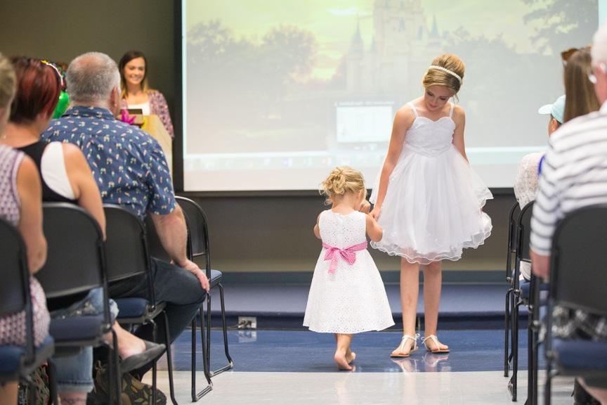 Two girls showcase white dresses during Moraine Park fashion show