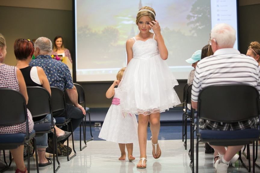 Two young girls walk down runway in white dresses at MPTC cosmetology fashion show