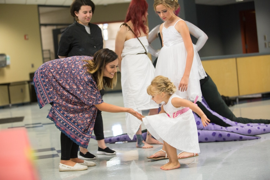 Young girl gives mother high five at Moraine Park summer fashion show