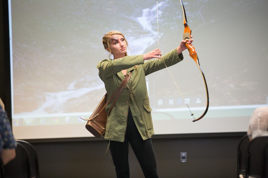 Model at Moraine Park fashion show pulls back bow and arrow to mimic Hunger Games