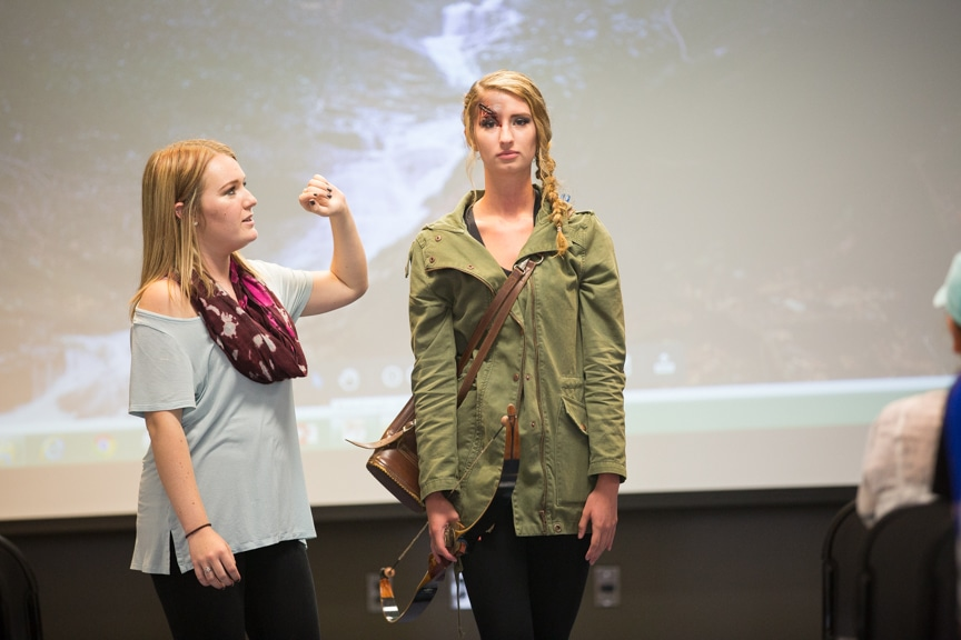 Student discusses details of hairstyle while model stands next to her at MPTC fashion show