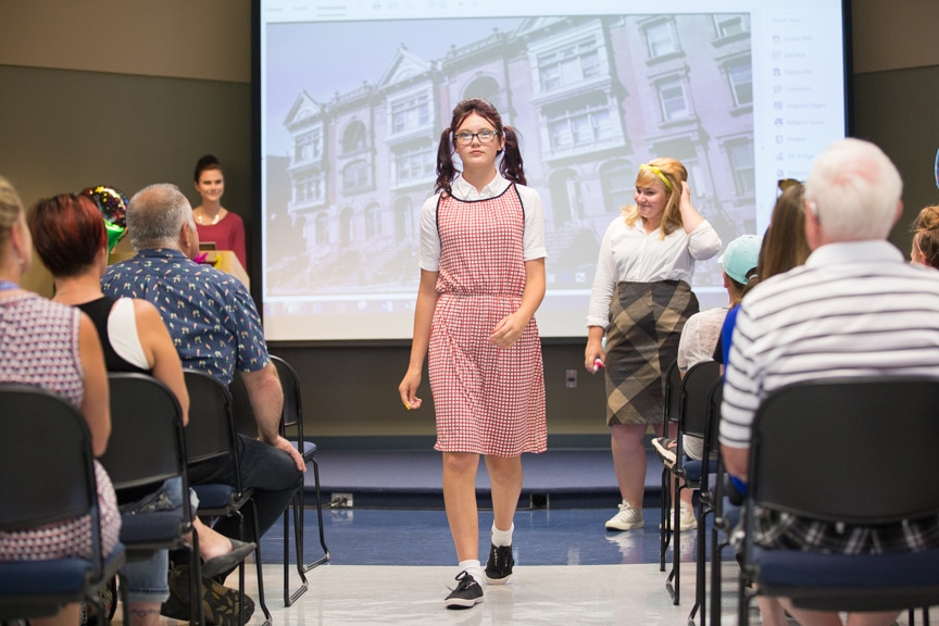 Girl in checkered dress walks down runway at Moraine Park fashion show