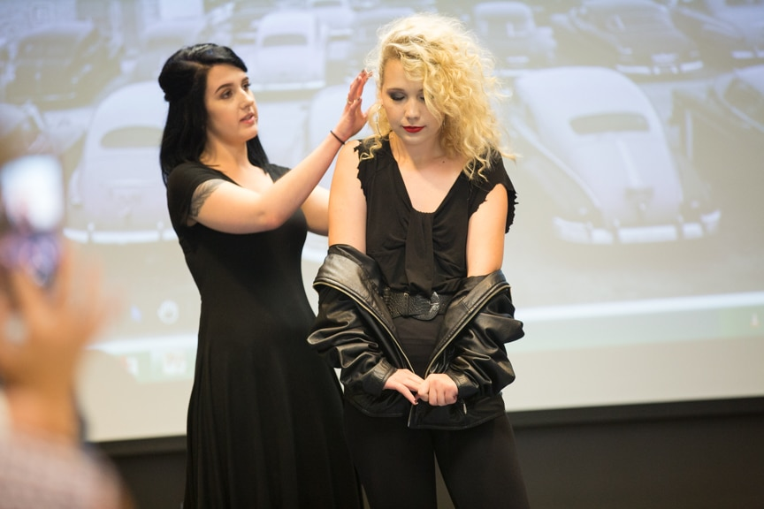 Student points out hairstyle details of model with blonde hair at Moraine Park summer fashion show