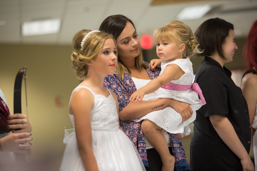 Cosmetology student holds young daughter during fashion show
