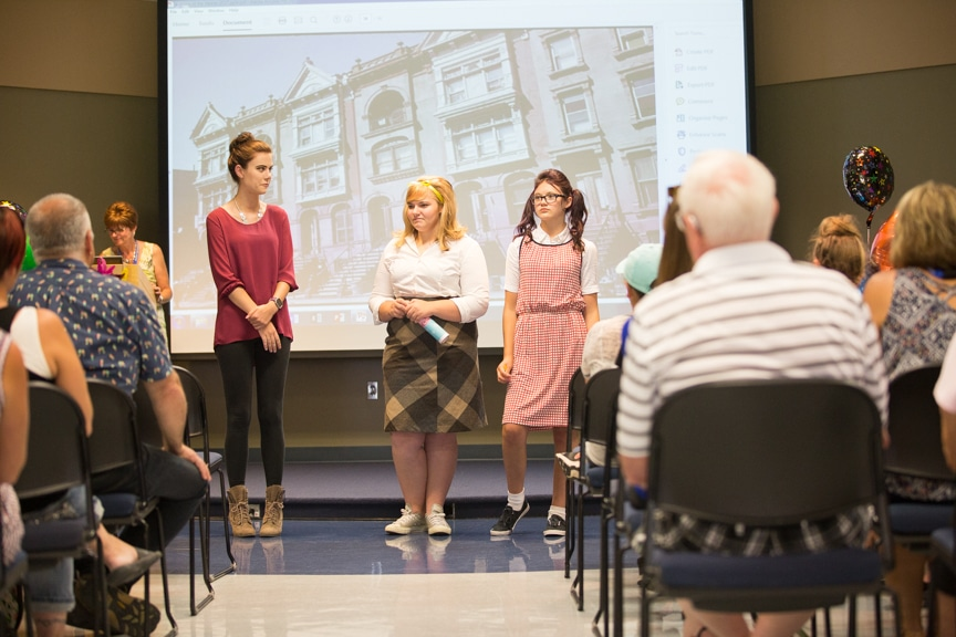Cosmetology student stands next to two models dressed in 1960s clothing during Moraine Park fashion show