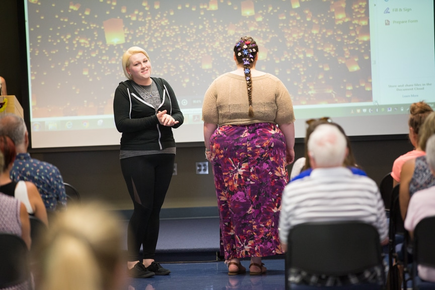 Cosmetology student discusses hairstyle while model turns back to show off poney tail at MPTC fashion show