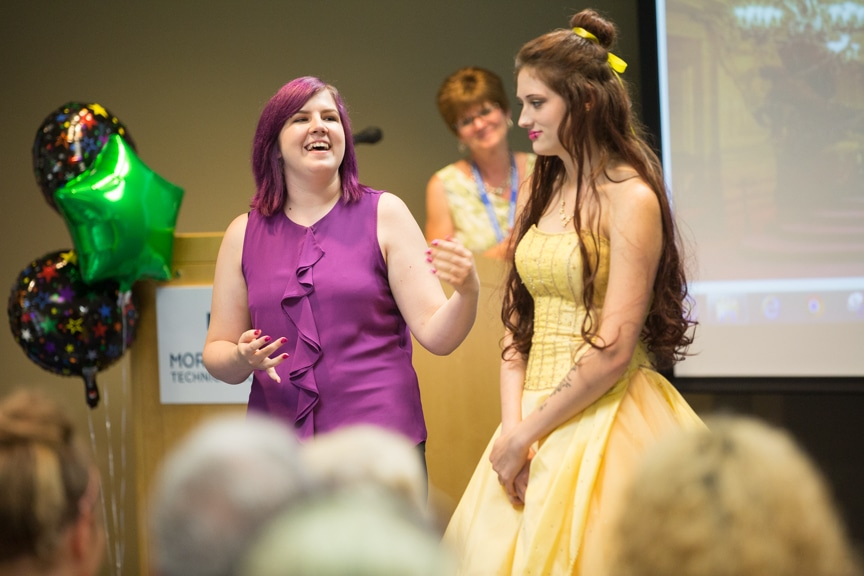 Student laughs while pointing out features of Beauty and the Beast-inspired hairdo on model