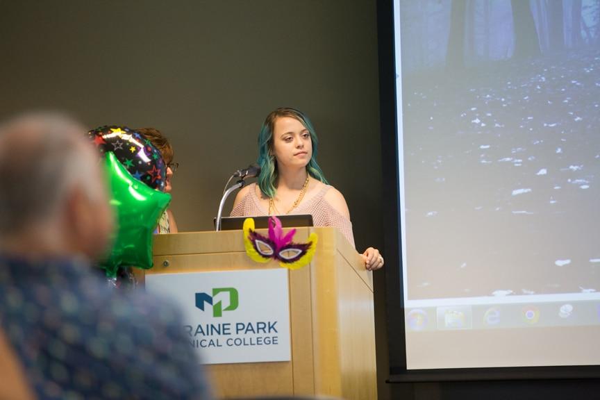 Student speaks at podium during Moraine Park fashion show