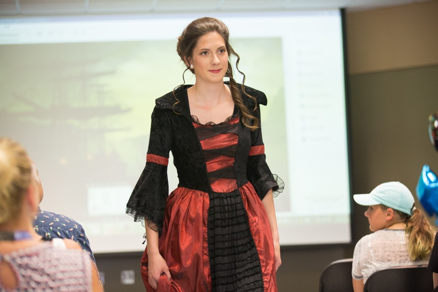 Model walks down runway with red and black dress on at Moraine Park summer fashion show