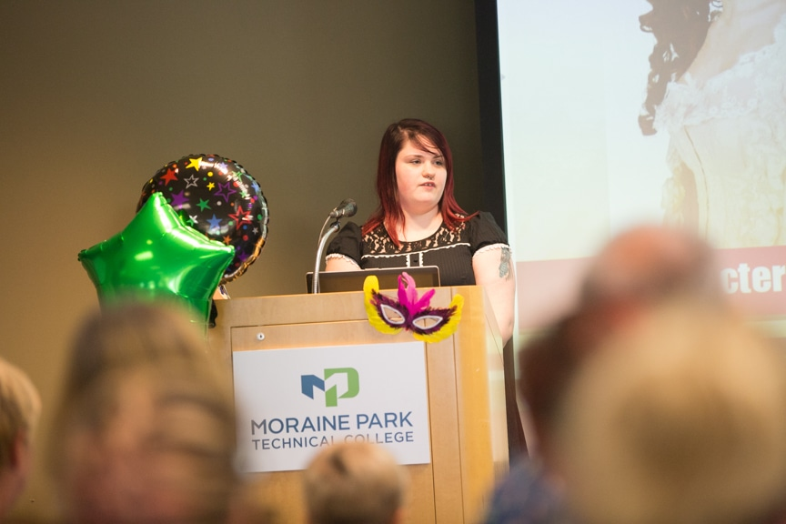 Student speaks form podium at Moraine Park summer fashion show