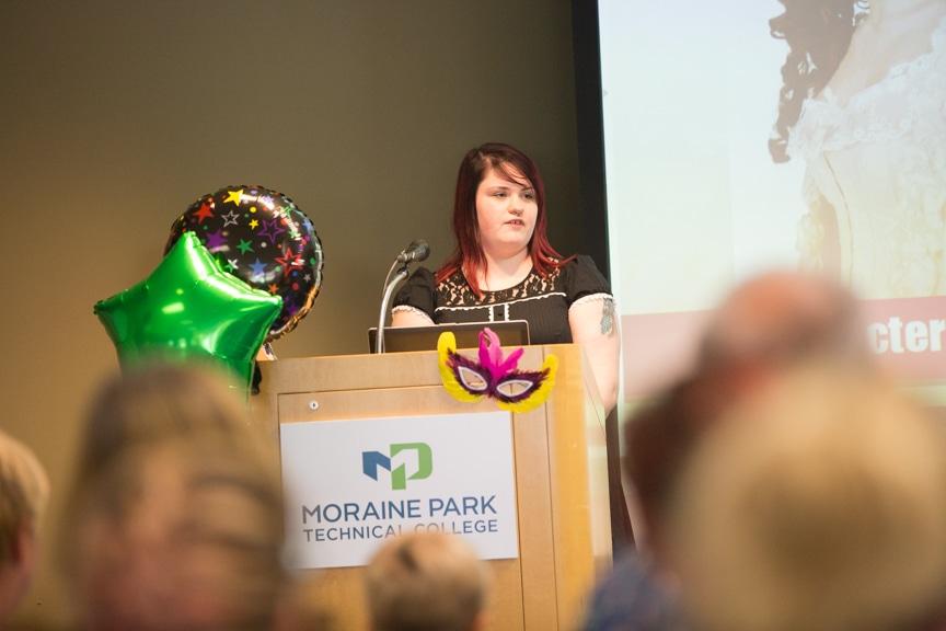 Student speaks form podium at Moraine Park summer fashion show