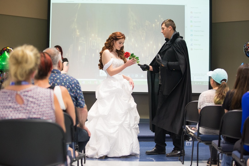 Male and female model dressed as Phantom of the Opera characters exchange a rose at Moraine Park fashion show