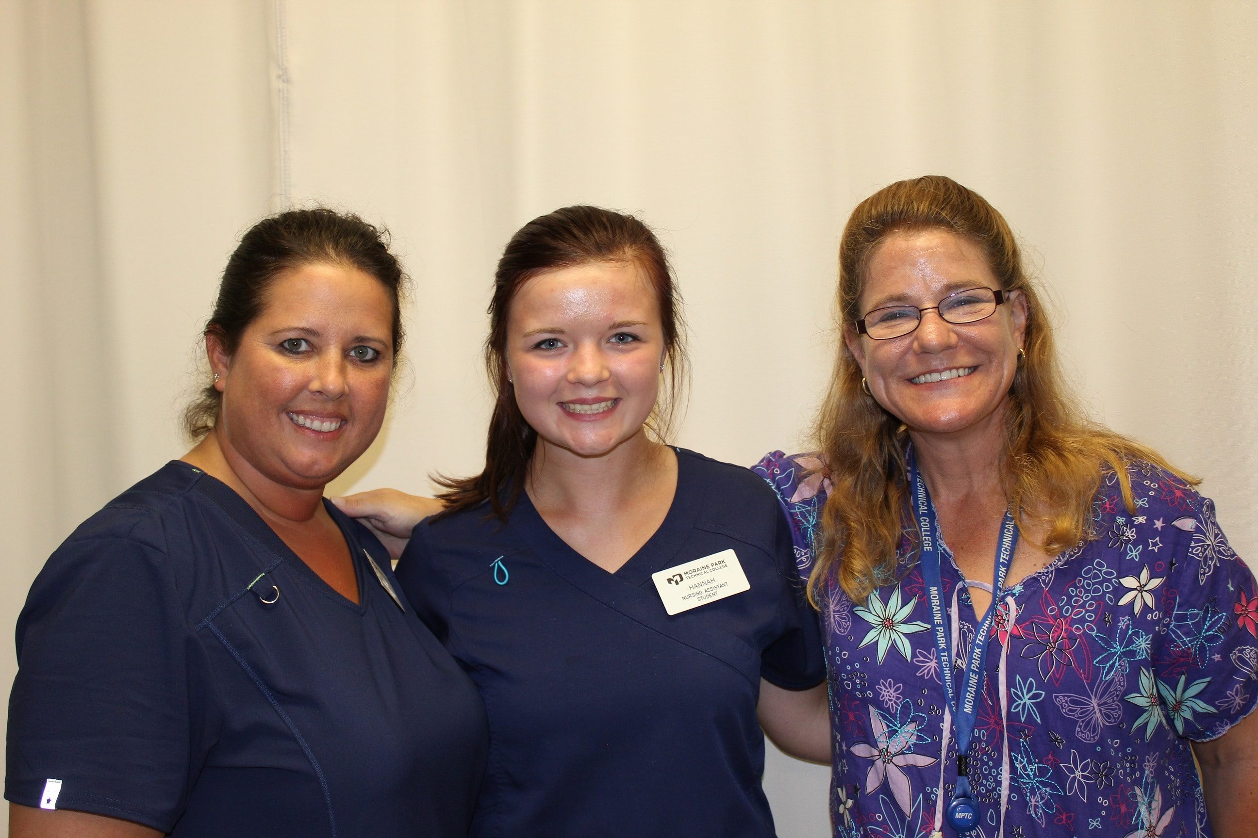 Two students from CNA boot camp pose for picture with instructor