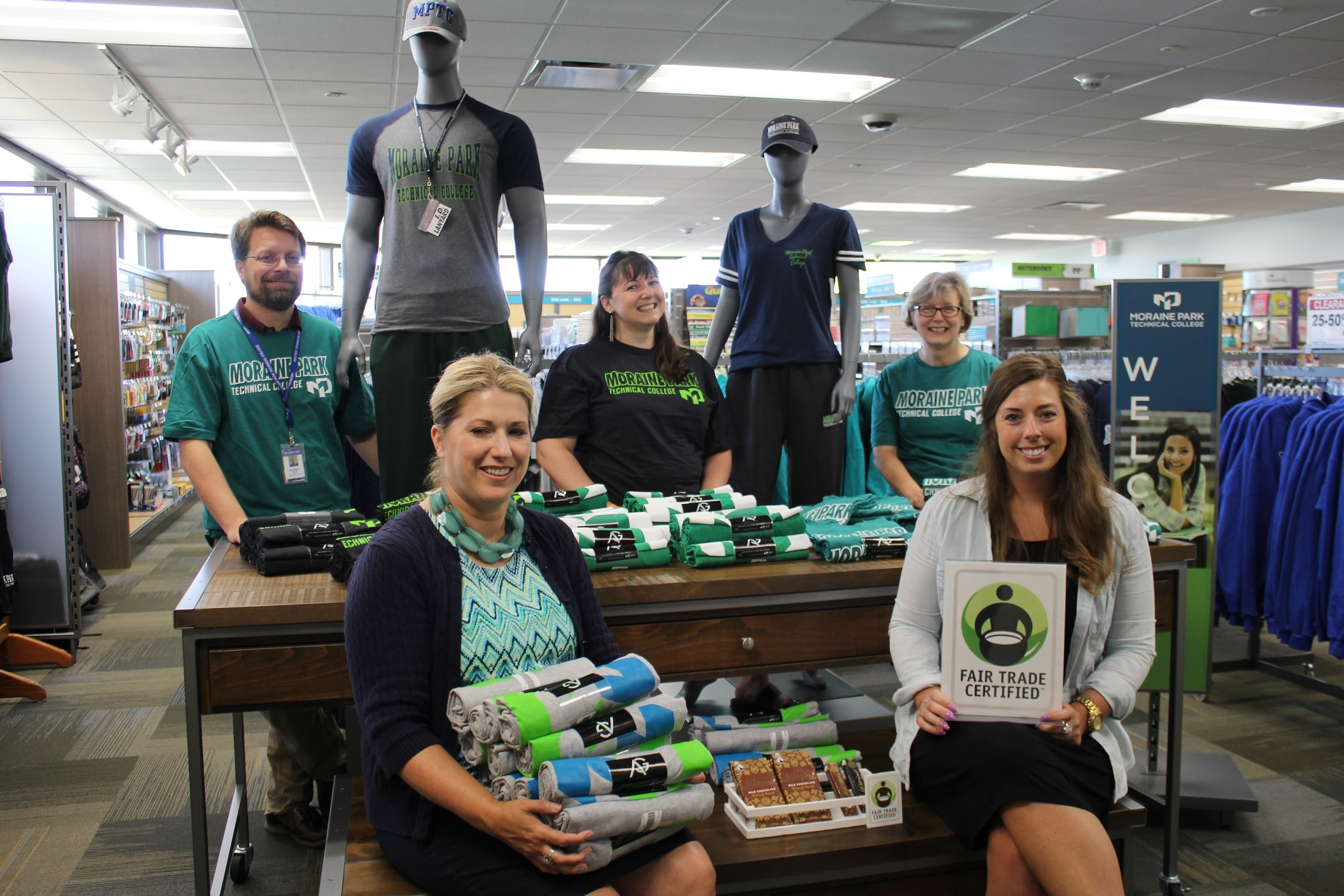 Moraine Park staff wearing logo wear and holding Fair Trade signage in bookstore.