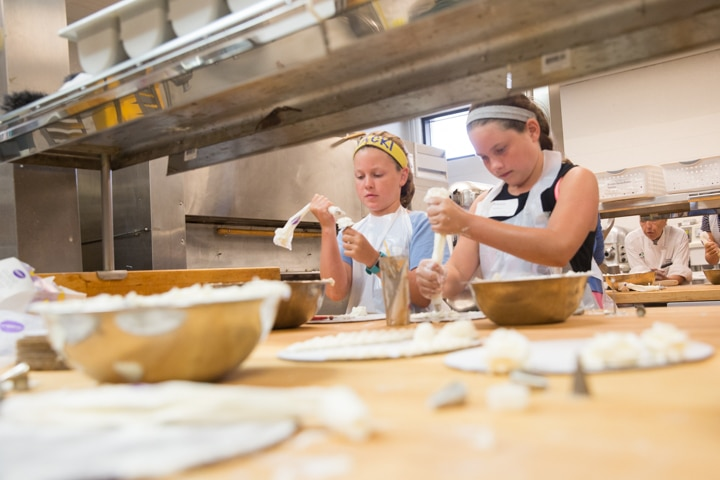 Two girls work on icing techniques during Moraine Park Tech Knowledge College culinary activity