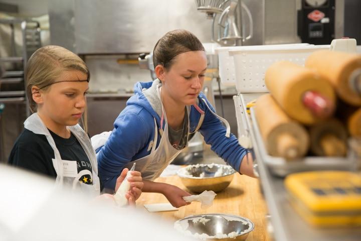 Girl reaches for item in kitchen at Moraine Park TKC