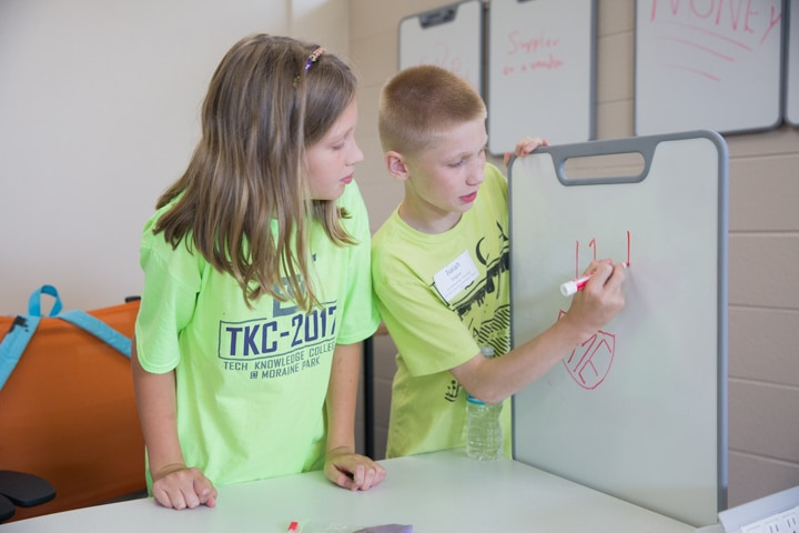 Two students draw logos on whiteboard during business management activity at Moraine Park summer camp