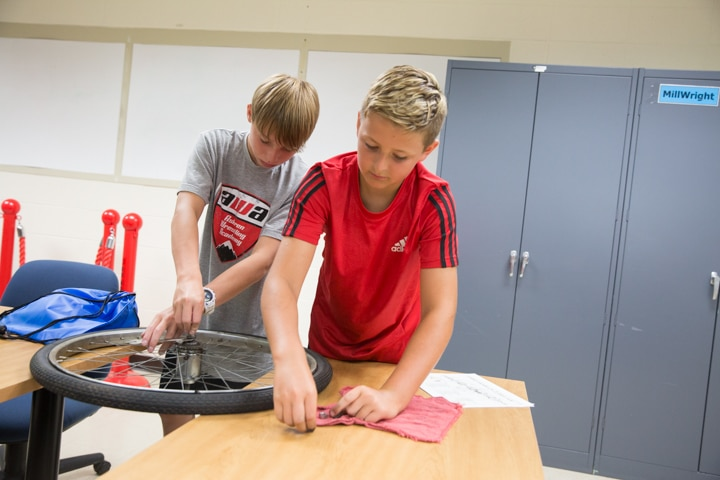 Two boys try to assemble bike tire at Moraine Park Tech Knowledge College