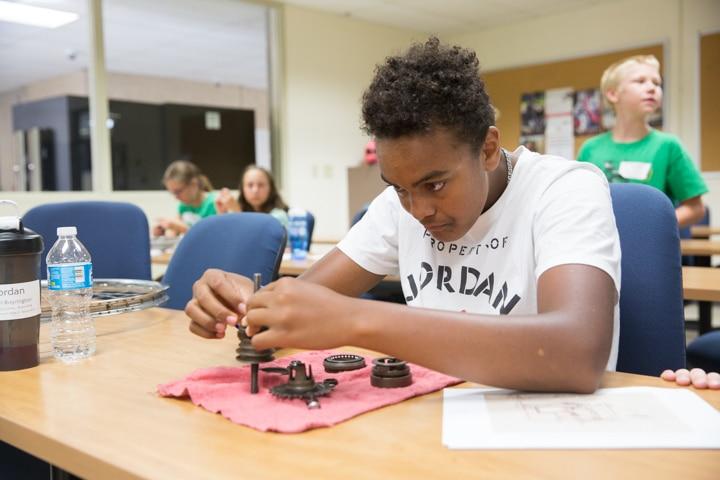 Boy places bike tire parts together at Moraine Park Tech Knowledge College