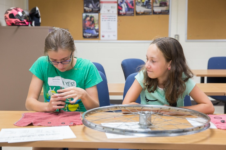 Girls assemble bike tire parts at Moraine Park summer camp