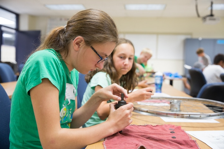 Girls work with bike parts at Moraine Park TKC summer camp